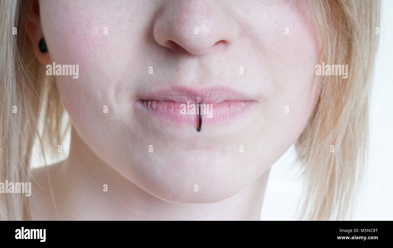 pierced female lips with vertical labret piercing or lip ring - Stock Image