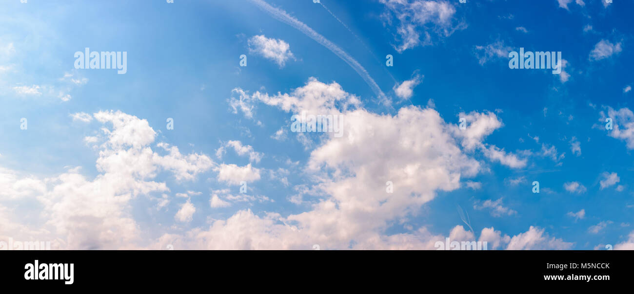amazing cloud formations on a bright blue sky. beautiful side lit cloudscape panorama in springtime - Stock Image