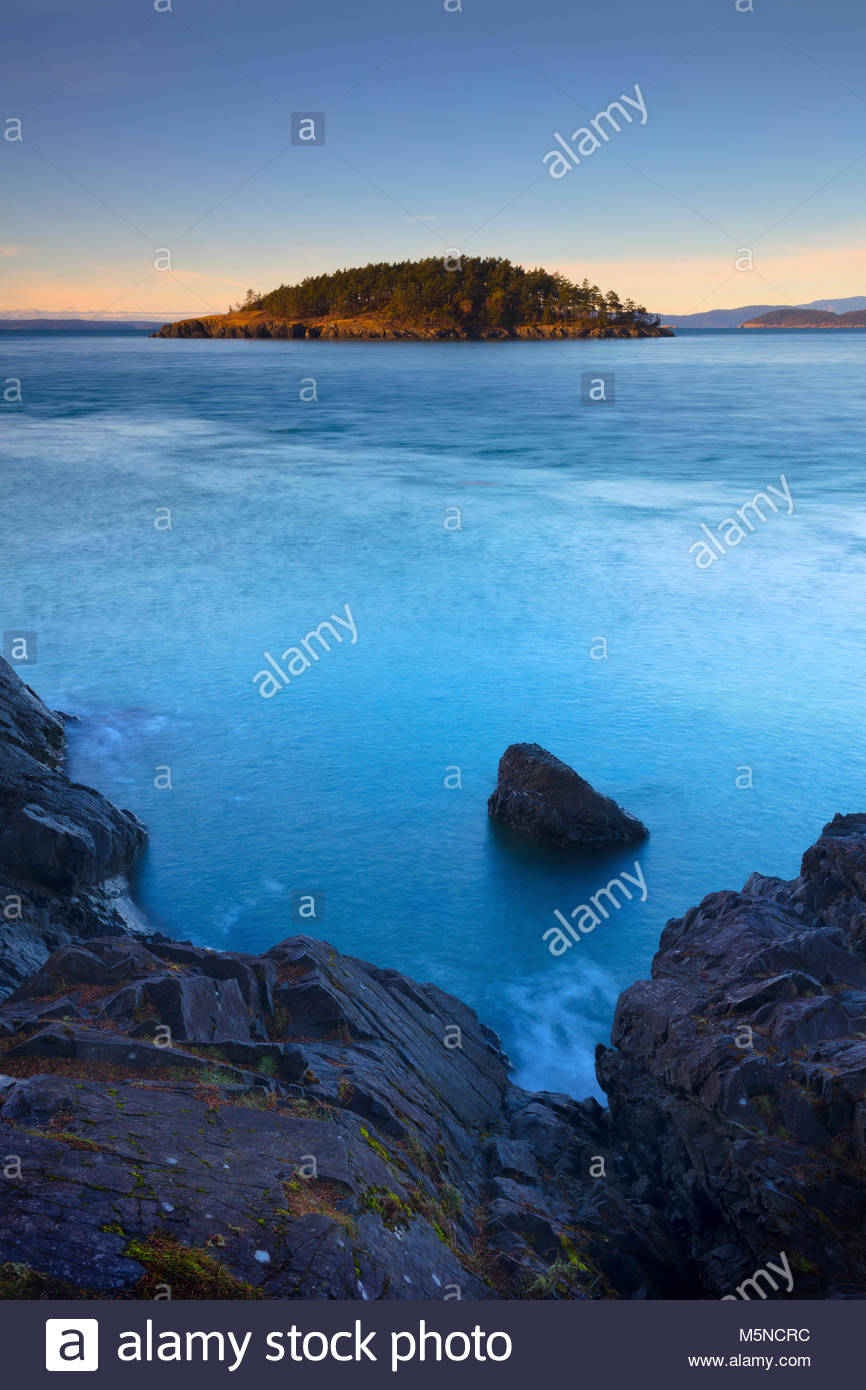 The rugged Deception Island is visible across Deception Pass from near North Beach in Deception Pass State Park - Stock Image