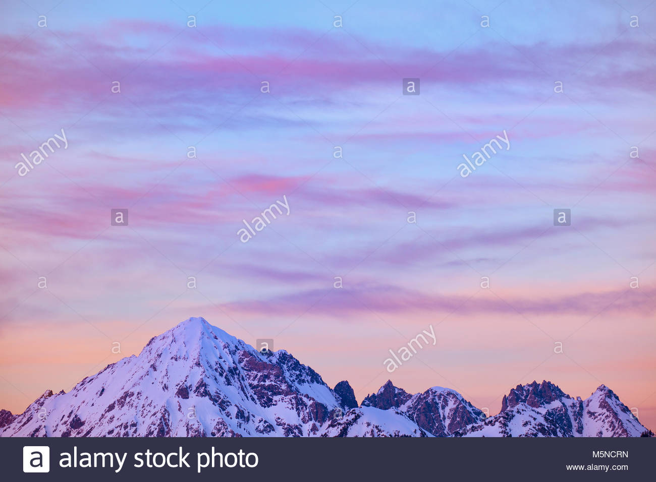 A band of cirrus clouds take on pastel colors at sunset in the sky over Mount Larrabee and the Boulder Peaks in - Stock Image