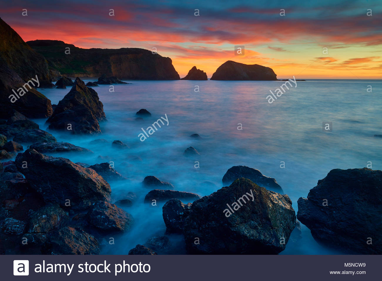 A fiery sunset colors the sky over Bird Island and the southern cliffs of the Marin Headlands, part of the Golden - Stock Image