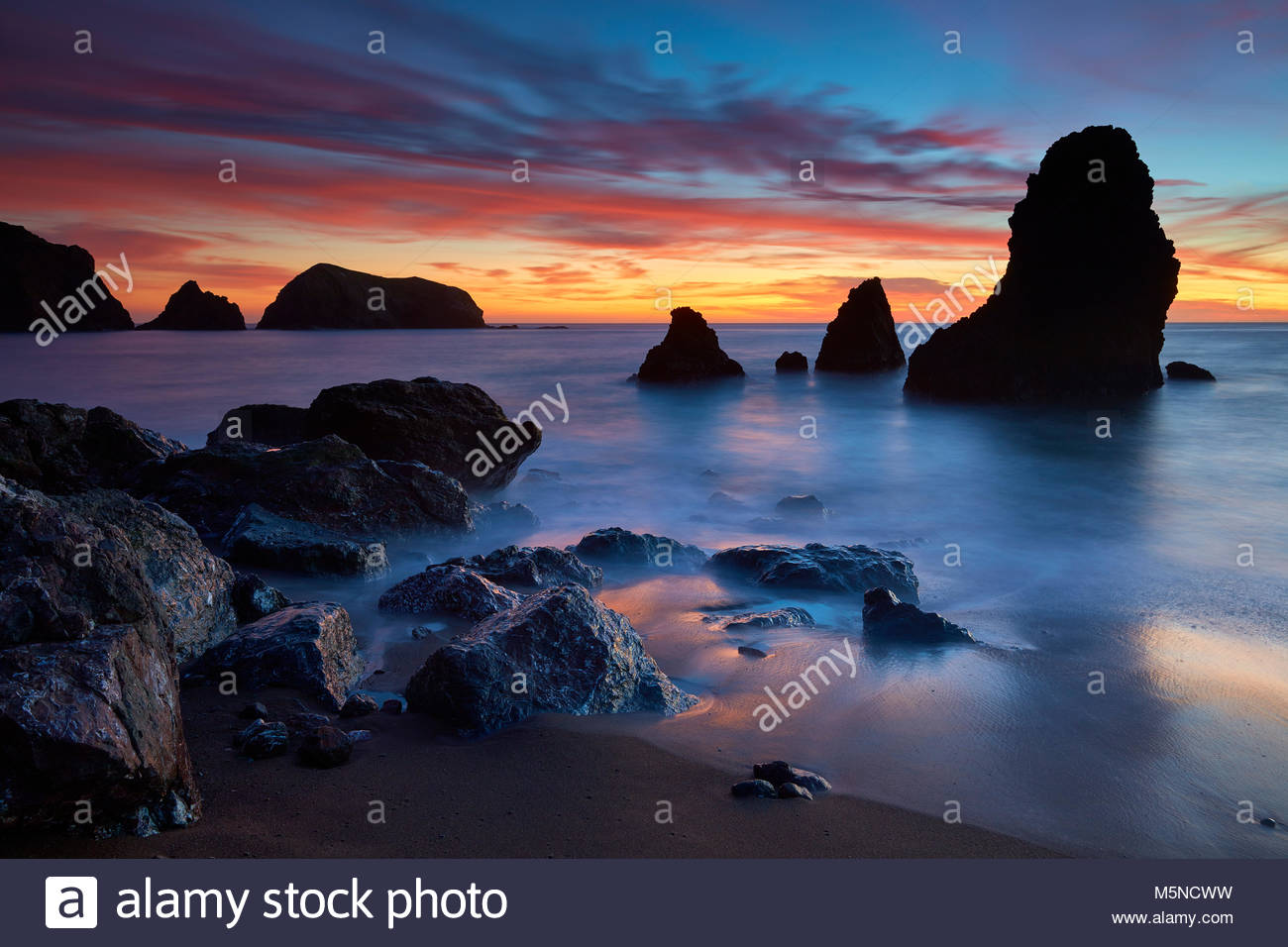 A fiery sunset stretches across Rodeo Cove, reaching from the sea stacks to Bird Island in the Marin Headlands near - Stock Image