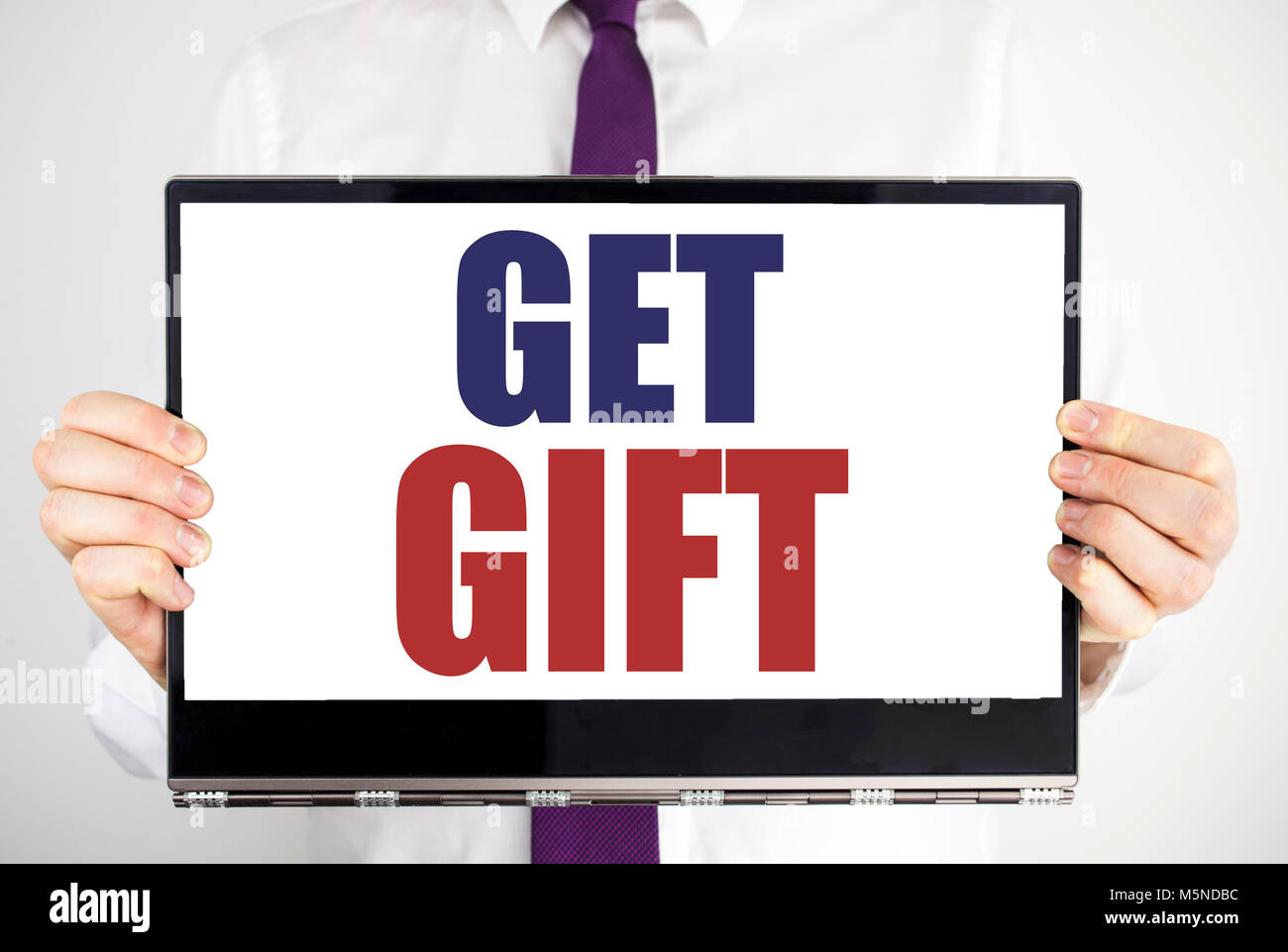 Word, writing Get Gift. Business concept for Free Shoping Coupon Written on tablet laptop holding by man blurred - Stock Image