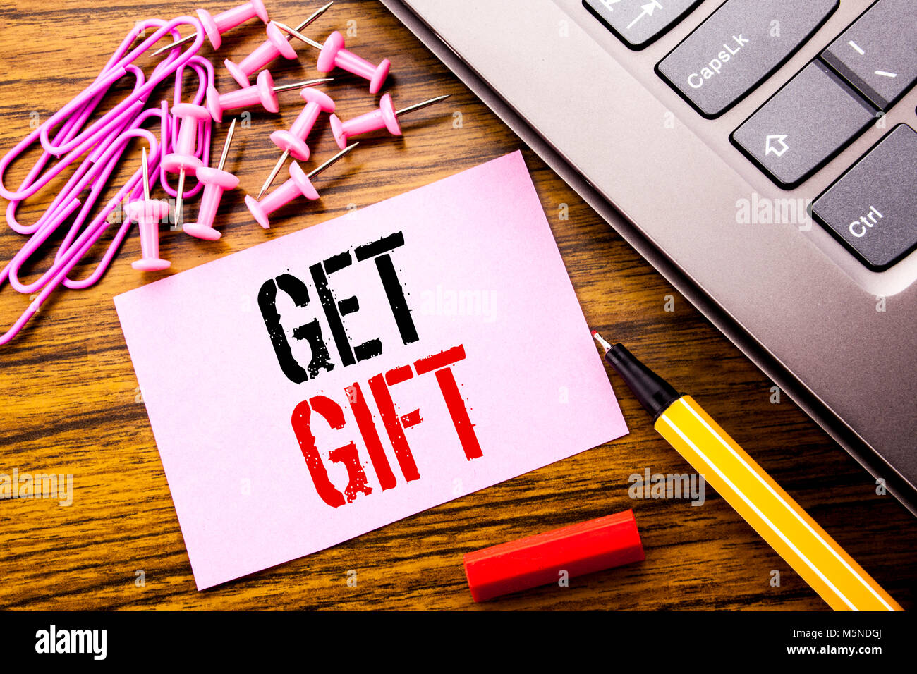 Handwritten text showing Get Gift. Business concept for Free Shoping Coupon written on pink sticky note paper on - Stock Image