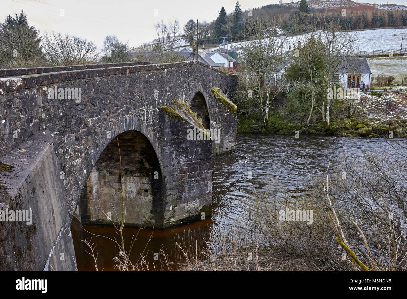 Looking from upstream at a wintery Westerkirk Bridge over the river Esk from the north bank. A category A listed - Stock Image
