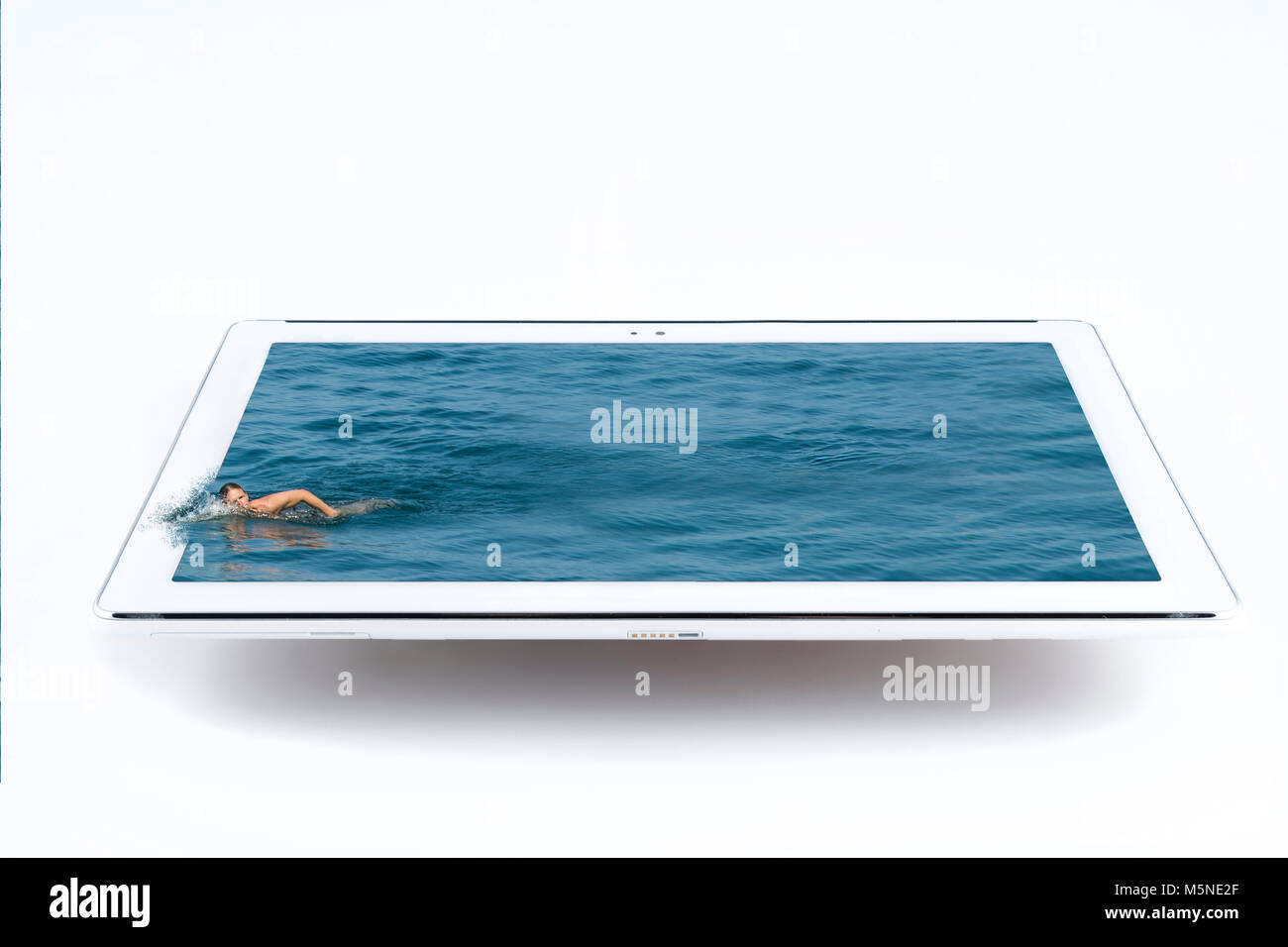 a swimmer in the water that bursts from the tablet - Stock Image