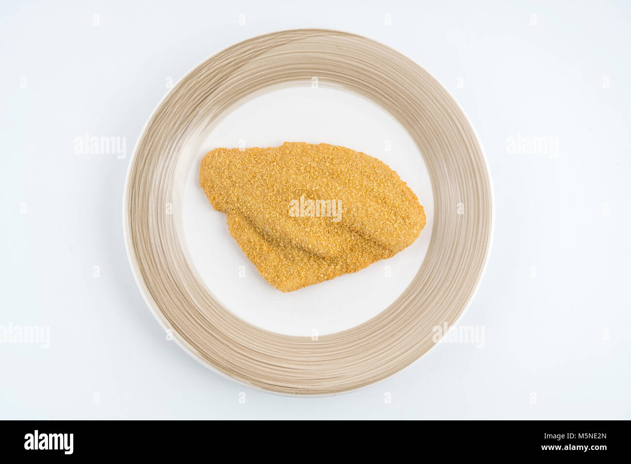 a fillet of plaice breaded frozen on the plate - Stock Image