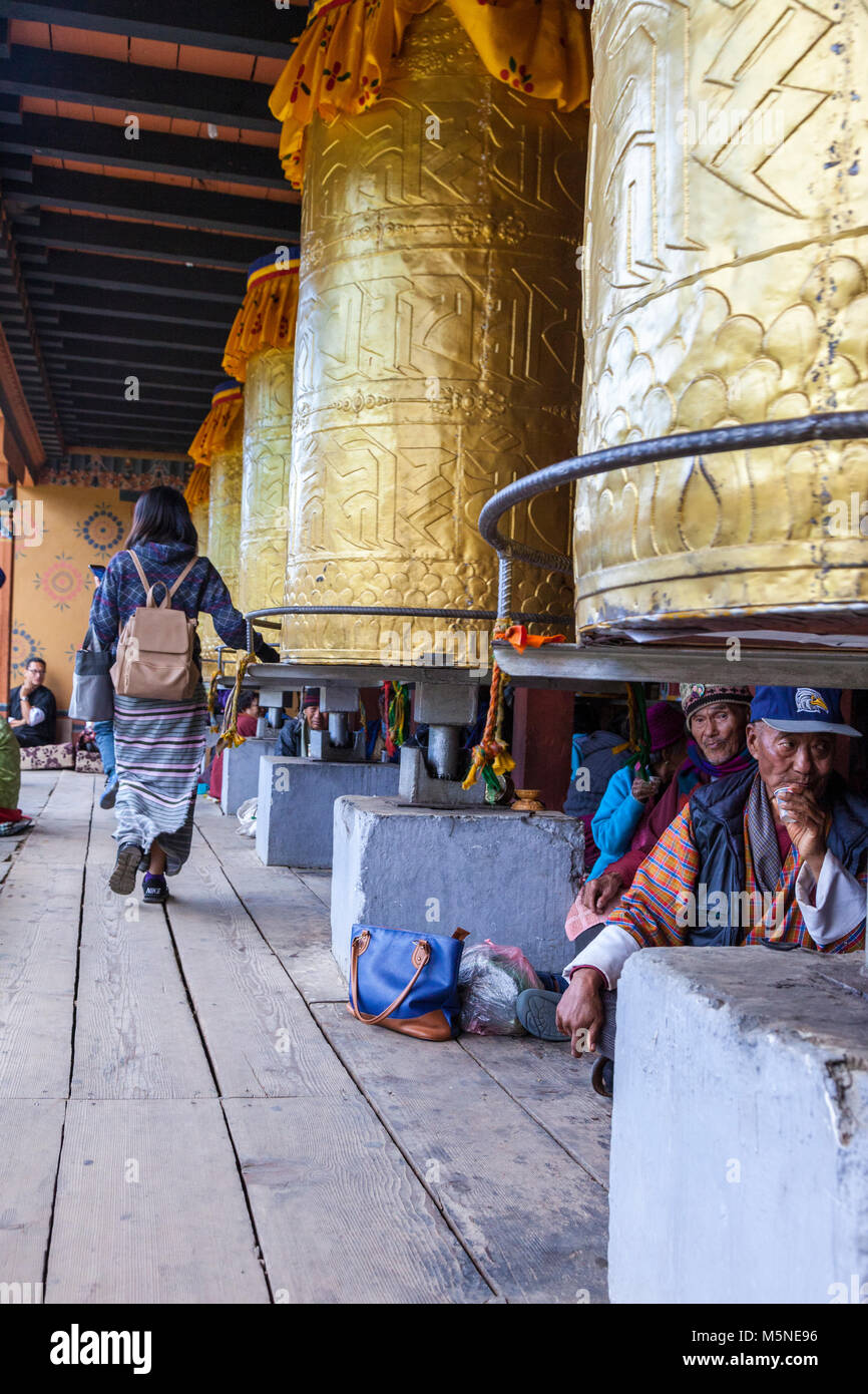 Thimphu, Bhutan.  Young Woman Turning Prayer Wheels at the National Memorial Chorten while Others Sit Underneath. Stock Photo