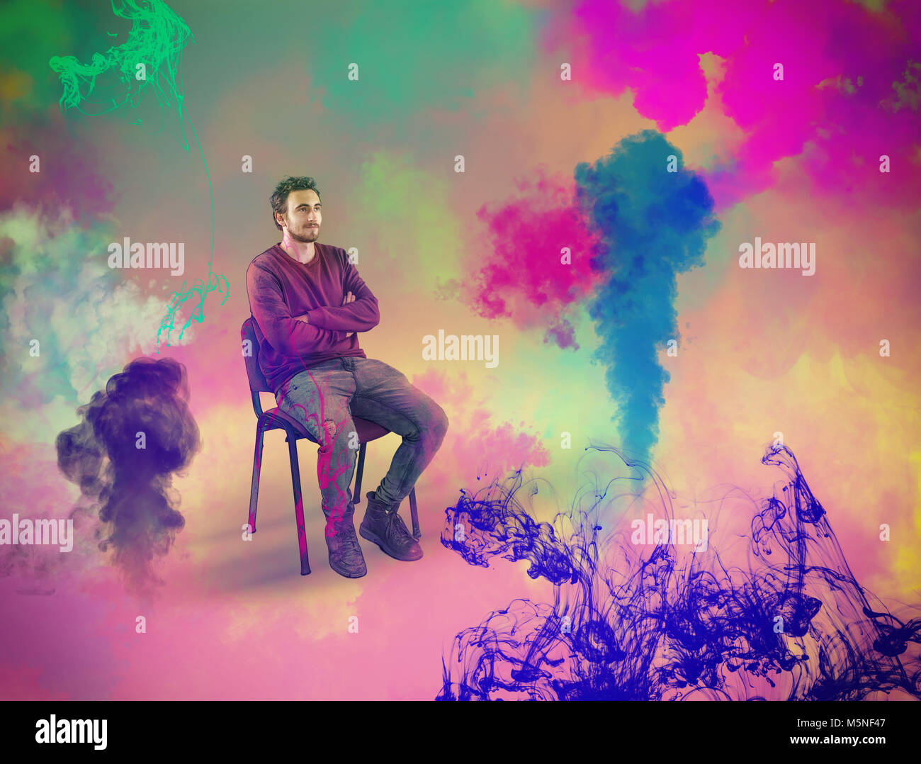 Young man sitting on chair while he visualize colorful ink and steam. The concept of creativity and visualization. - Stock Image