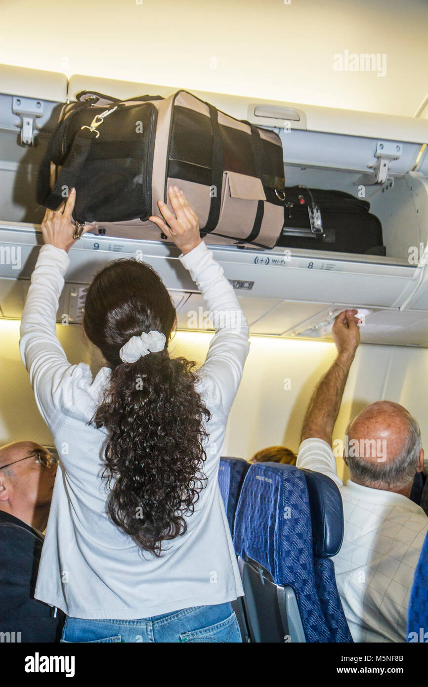 Miami Florida International Airport MIA Hispanic woman American Airlines onboard overhead luggage bin suitcase storing - Stock Image