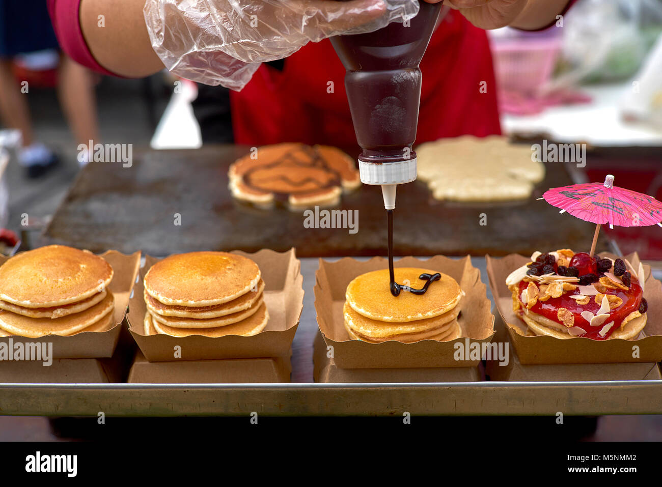 Thailand street food vendor preparing and decorating filled pancakes. Derived From American style  pancakes. 1 of - Stock Image