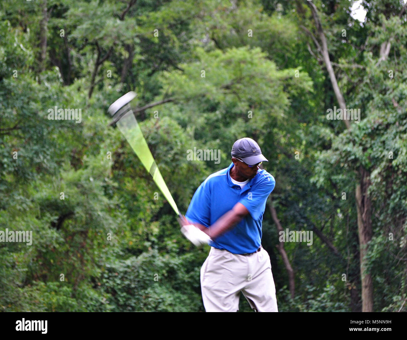 Male golfer teeing off with driver on a par 4 - Stock Image