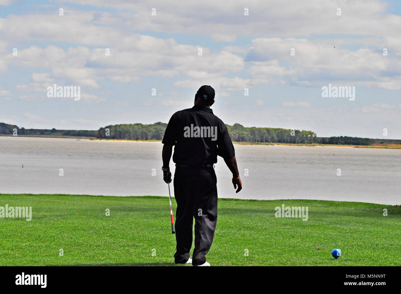 Golfer in Black teeing off on a par 3 - Stock Image