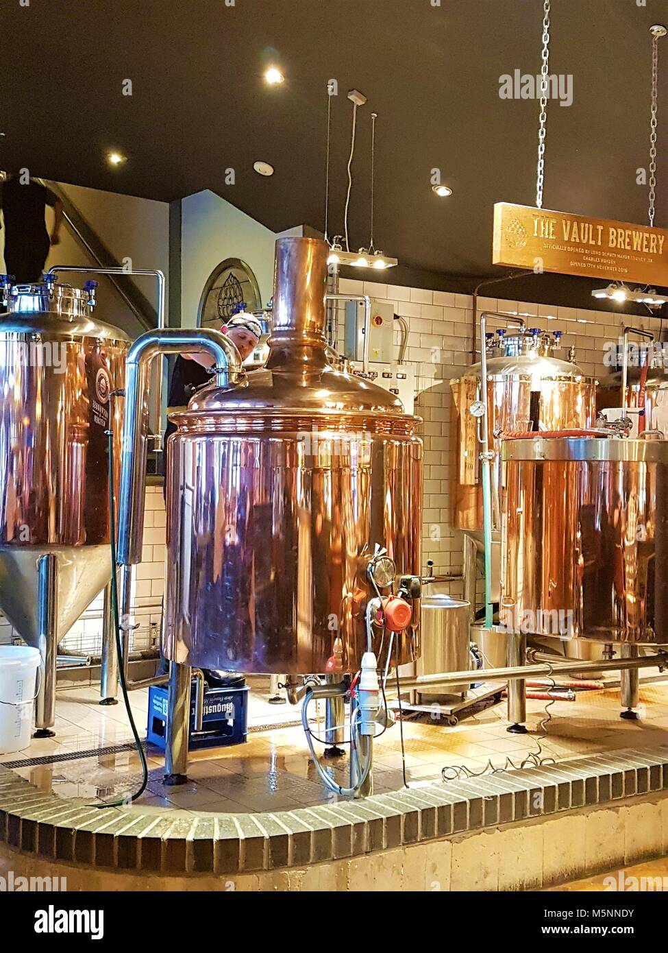 Man brewing beer in copper stills at the Brew House and Kitchen, Bedford, UK - Stock Image