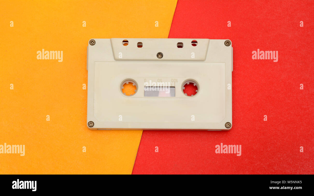 Retro audio compact cassette on yellow red background. - Stock Image