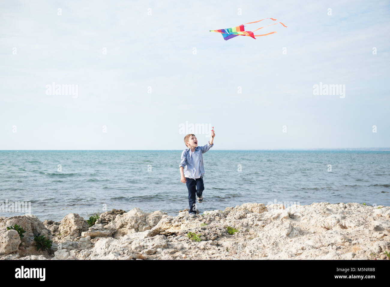 happy little boy with colored kite by the sea in California - Stock Image