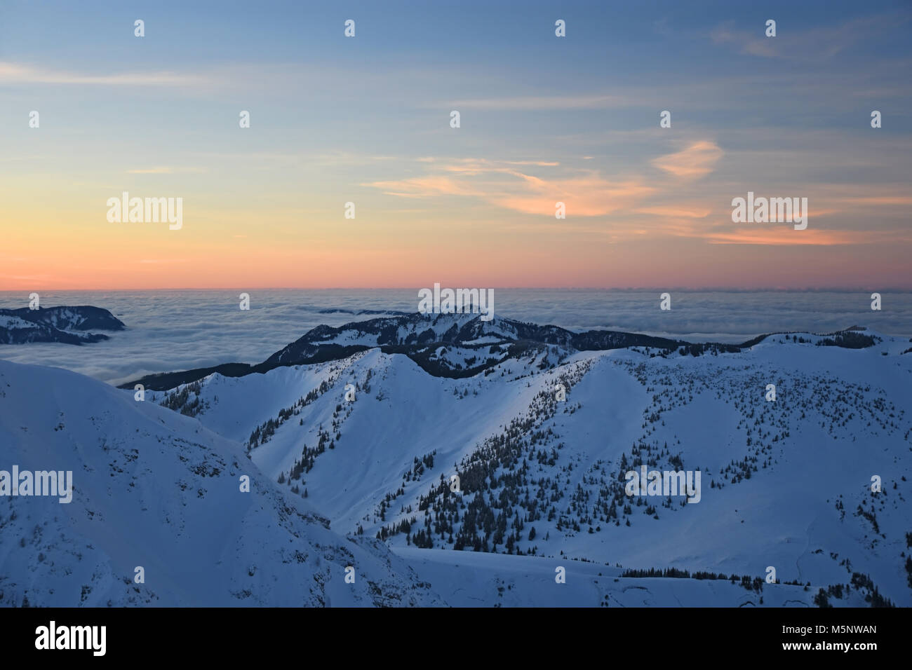 Colorful sunset at the summit of Ponten mountain in winter. View to Grünten mountain. Allgaeu Alps, Bavaria, Germany Stock Photo