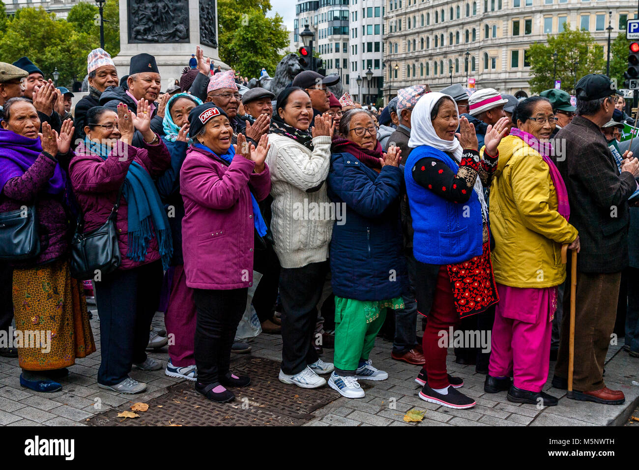 Ghurka women cheer football fans from across the Uk who are marching against extremism under the banner of the FLA - Stock Image