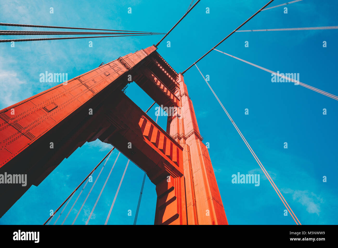 Beautiful low angle view of famous Golden Gate Bridge with blue sky and clouds on a sunny day in summer with retro - Stock Image