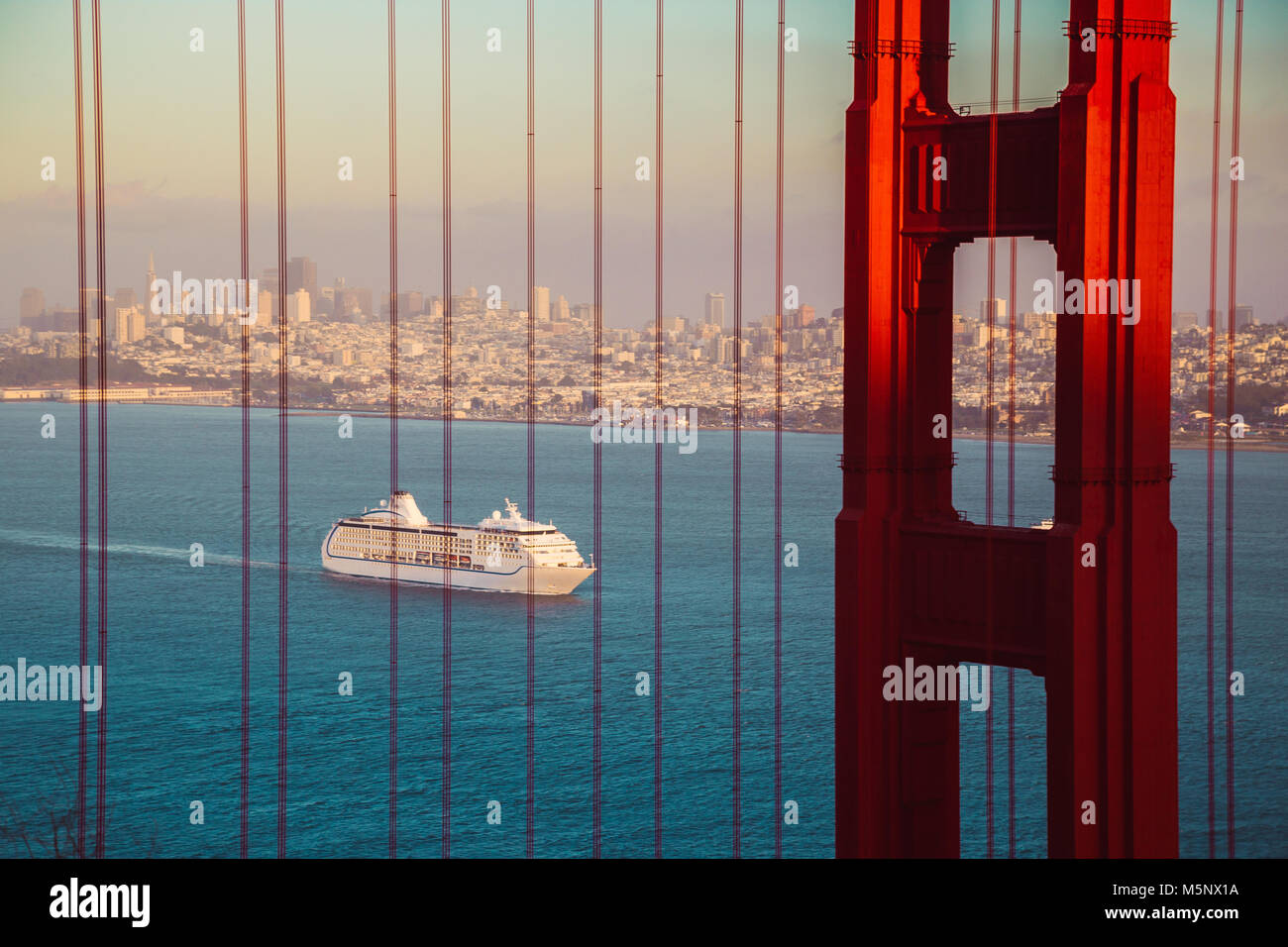Cruise ship at famous Golden Gate Bridge with the skyline of San Francisco in the background in golden evening light - Stock Image