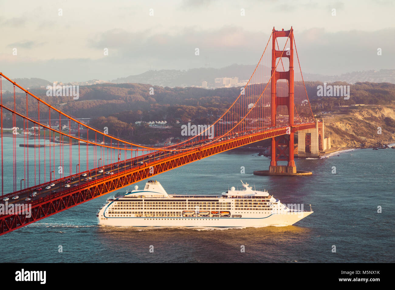Cruise ship passing famous Golden Gate Bridge with the skyline of San Francisco in the background in golden evening - Stock Image