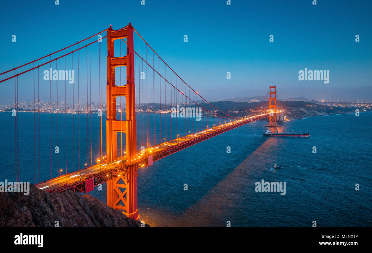 Classic panoramic view of famous Golden Gate with cargo freight ship in beautiful post sunset twilight during blue - Stock Image