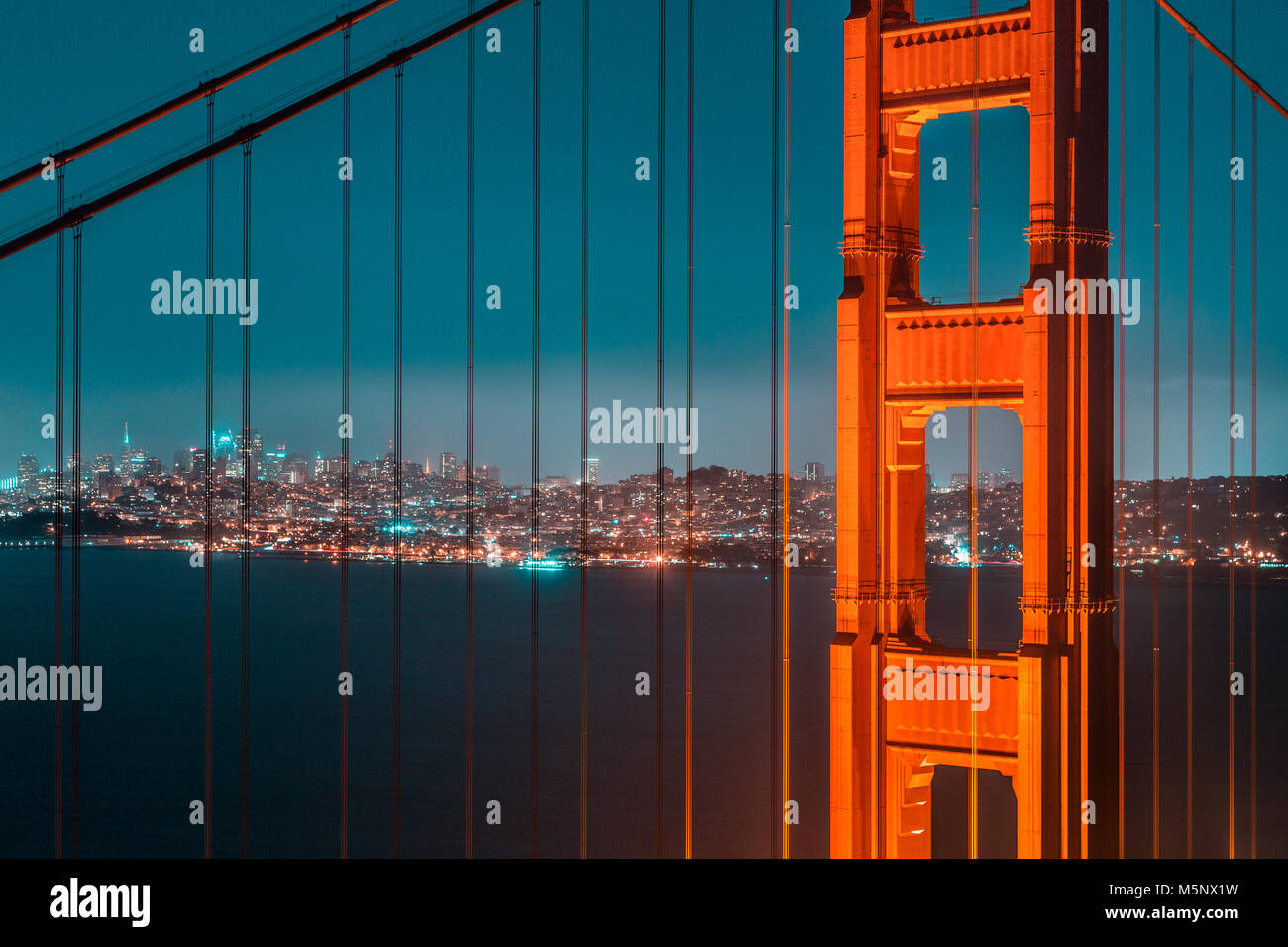 Classic view of famous Golden Gate Bridge with the skyline of San Francisco in the background in beautiful post - Stock Image