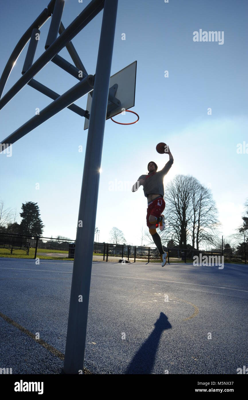 An outdoor shoot of a basketball player in Devizes, Wiltshire. Shot in natural sunlight on a basketball court. Wide depth of filed, good lighting. Stock Photo
