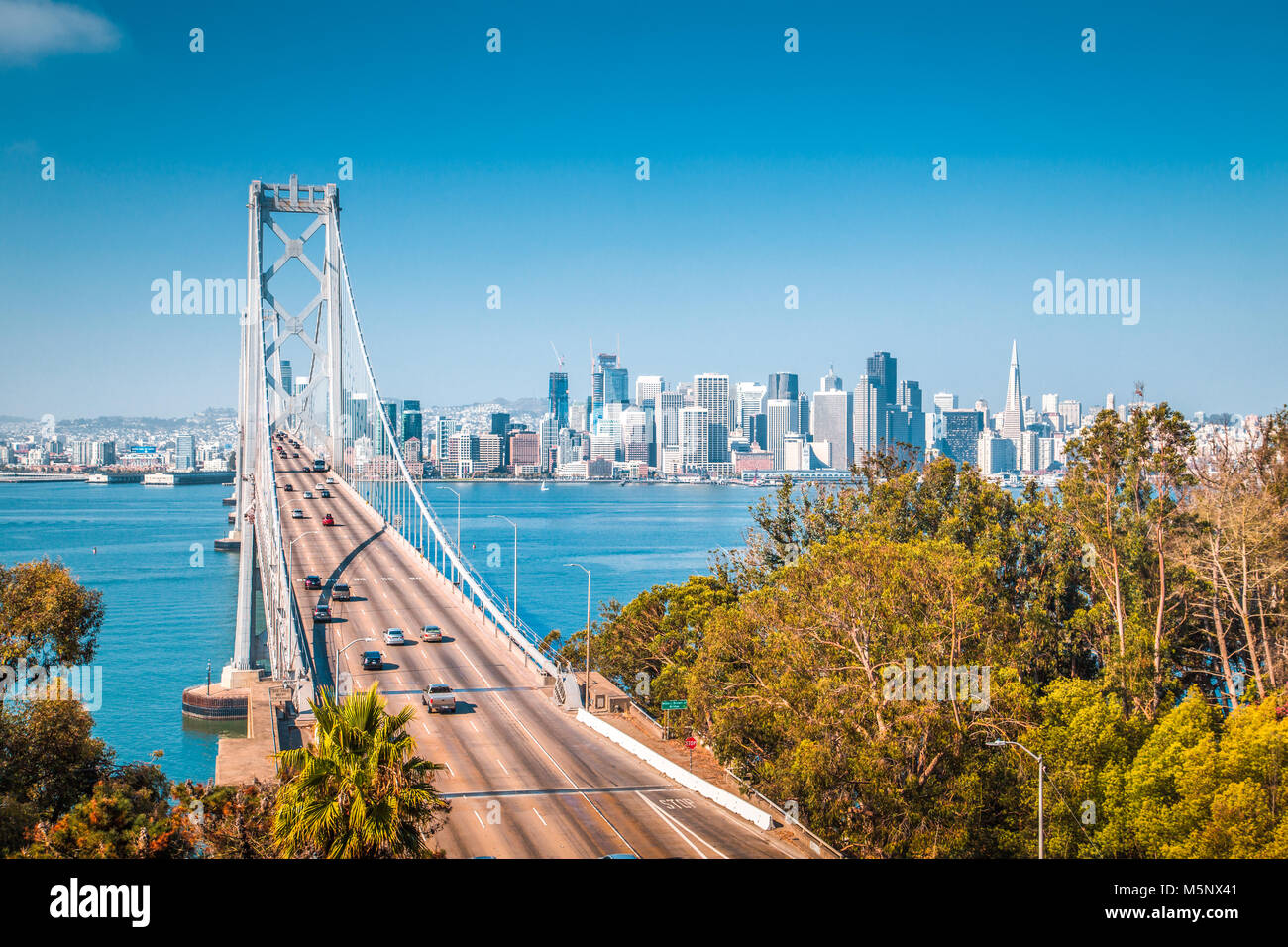 Classic panoramic view of San Francisco skyline with famous Oakland Bay Bridge illuminated on a beautiful sunny - Stock Image