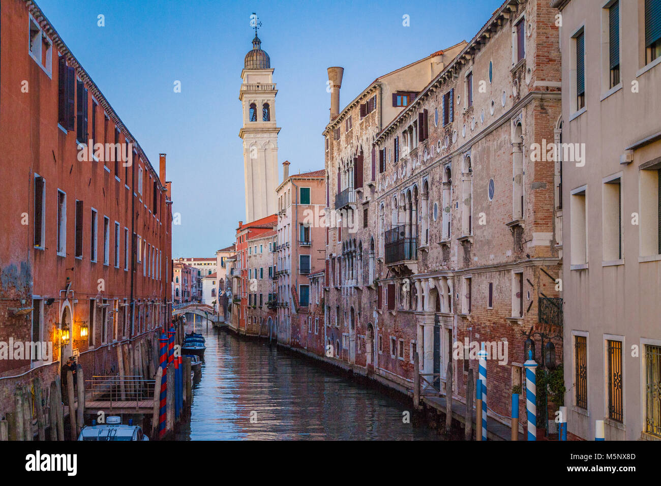 Classic Venice city scene with beautiful canal and church tower in the background in beautiful evening twilight - Stock Image