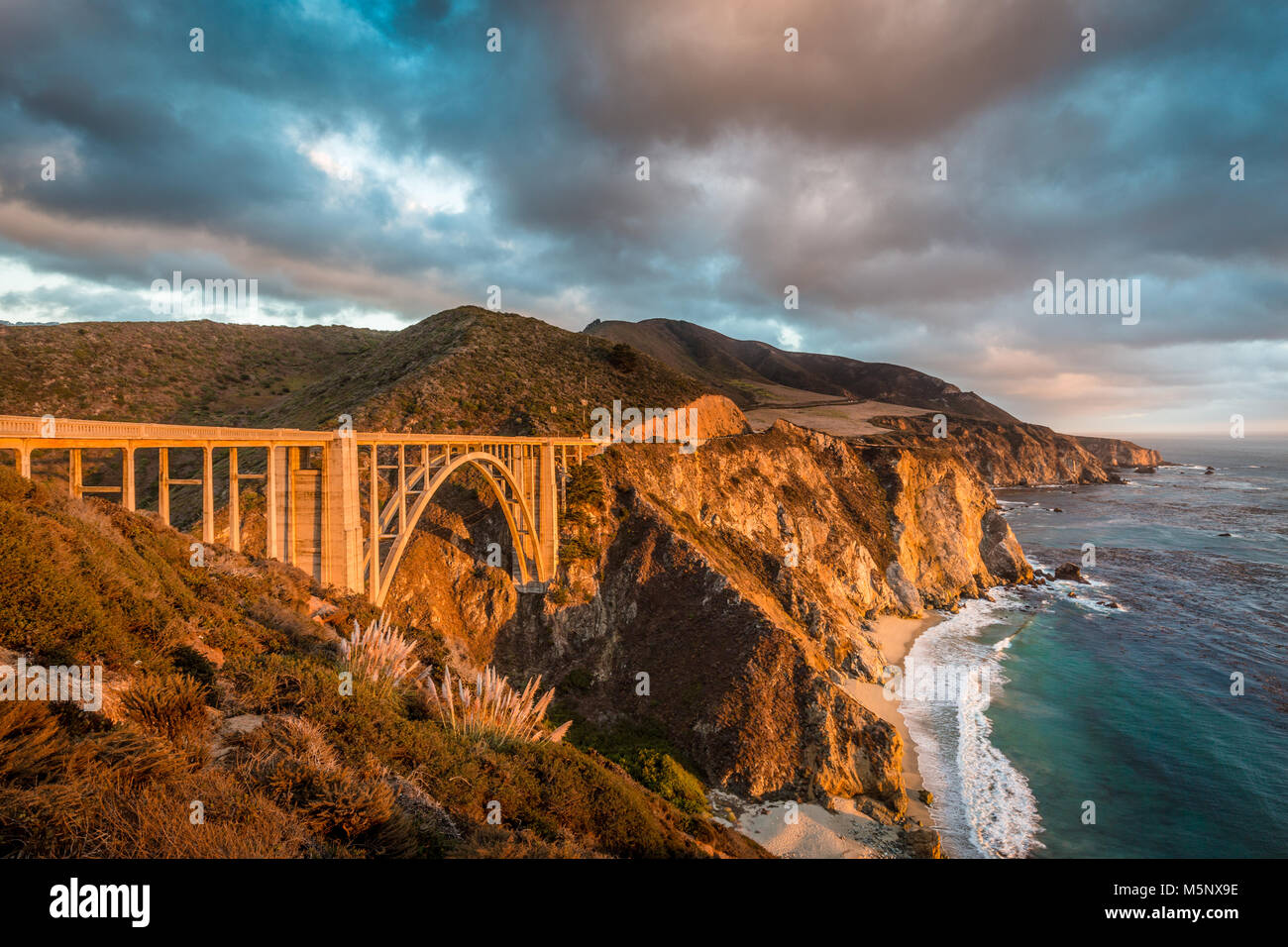 Panoramic view of historic Bixby Creek Bridge along world famous Highway 1 in beautiful golden evening light at - Stock Image