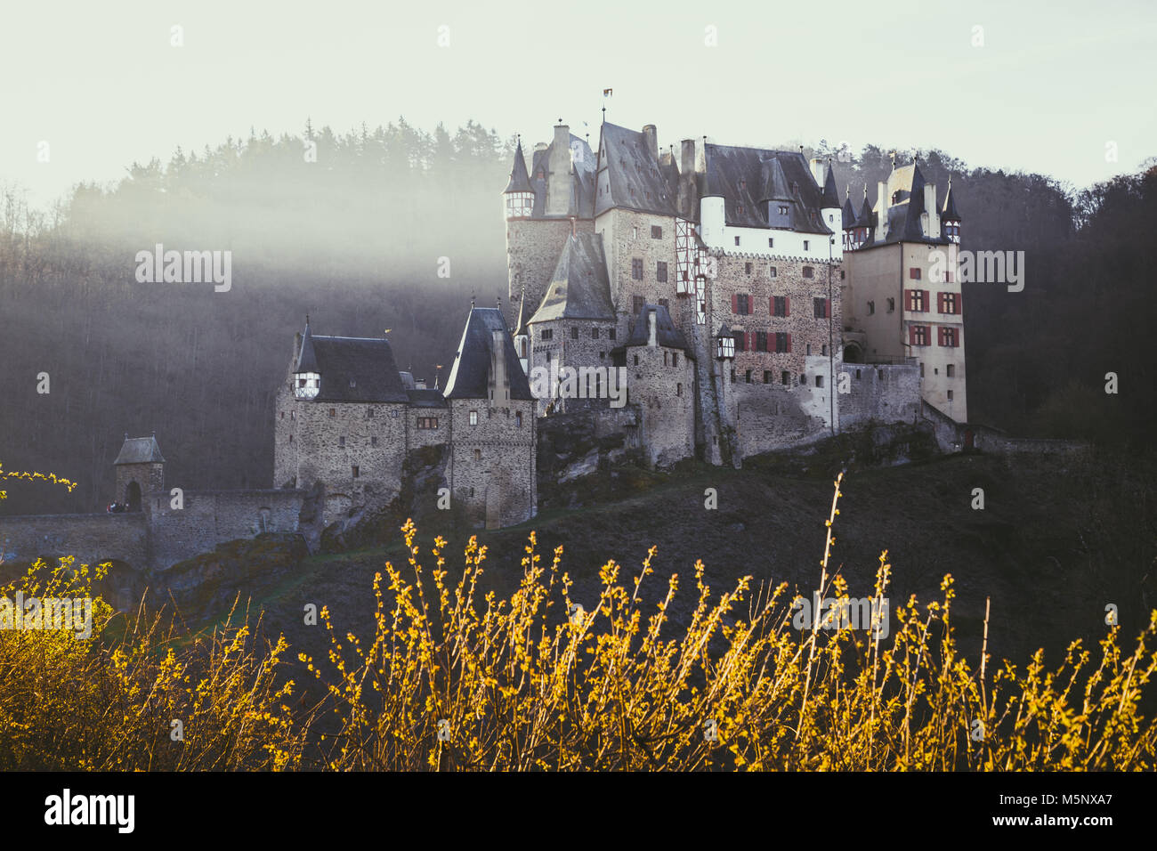 Beautiful view of famous Eltz Castle in scenic golden morning light at sunrise in fall with retro vintage VSCO style - Stock Image