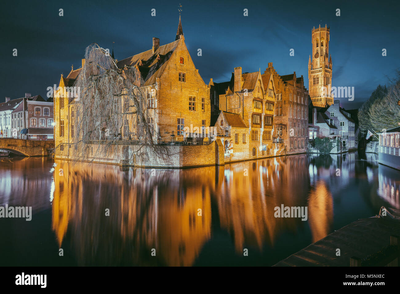 Hstoric city center of Brugge, often referred to as The Venice of the North, with famous Rozenhoedkaai illuminated - Stock Image