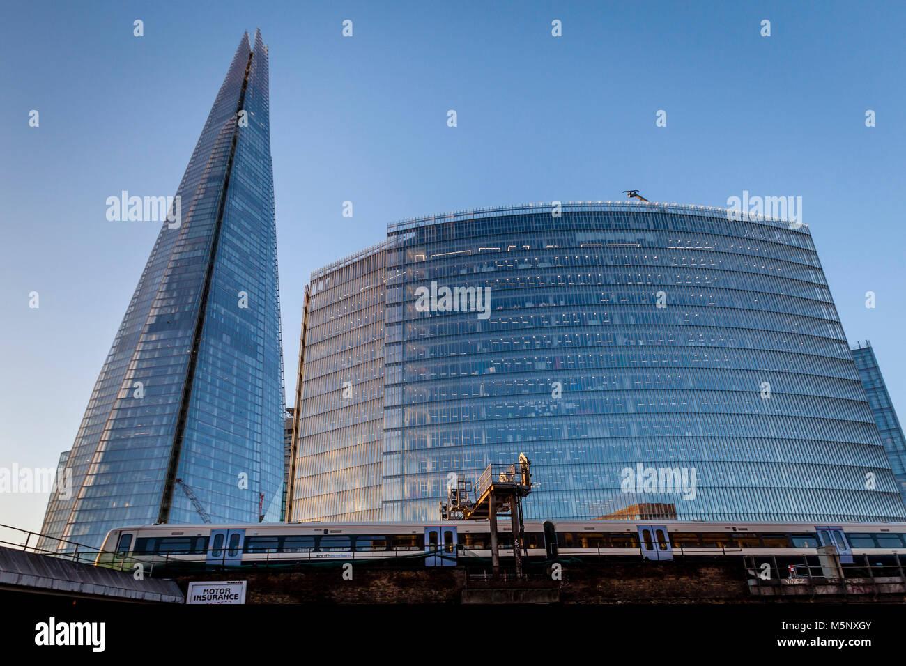 A Commuter Train Passes The Shard and The News Building, London Bridge Quarter, London, UK - Stock Image