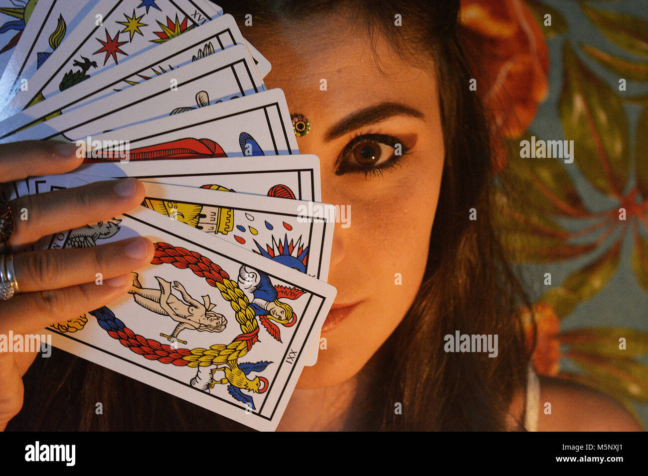 Woman with tarot deck on face - Stock Image