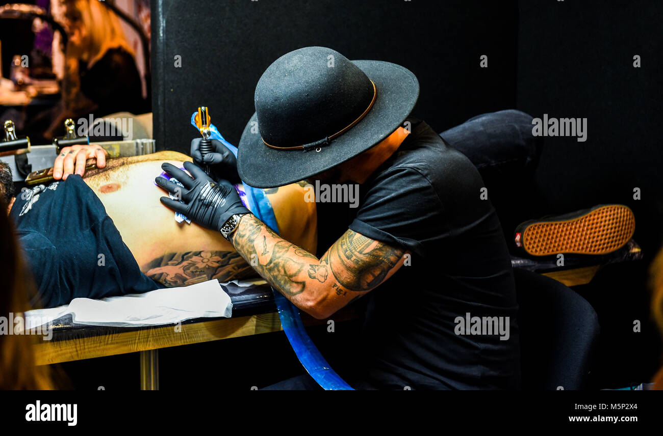 Brighton UK 25th February 2018 - Tattooists at work at the 11th annual Brighton Tattoo Convention held in the Brighton - Stock Image