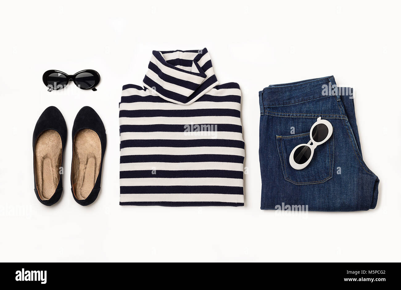 Fashion set of blue jeans, striped sweater, shoes and sunglsses on white background. Selective focus. - Stock Image