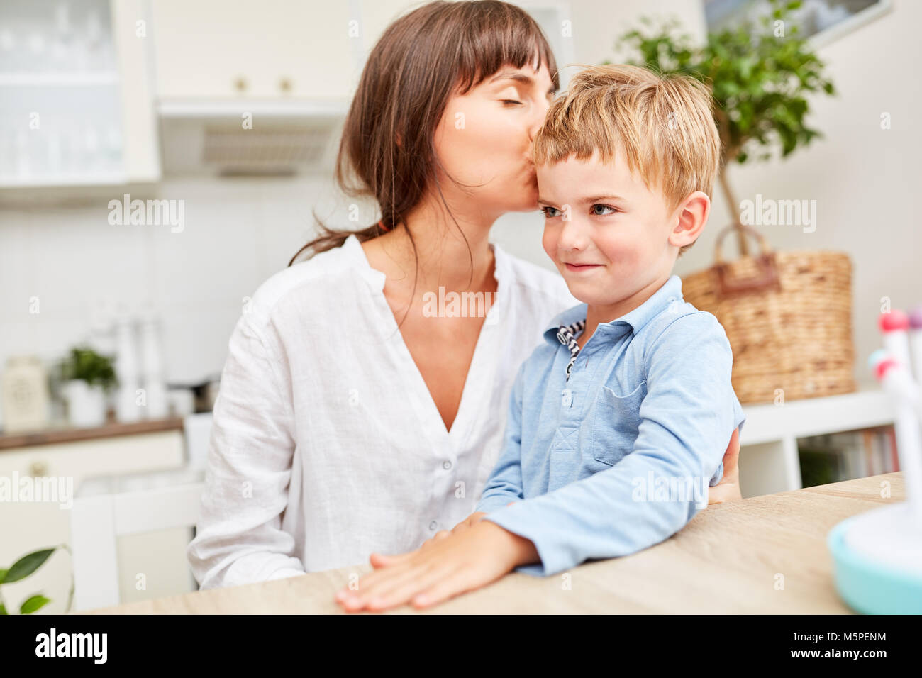 Happy mother lovingly kisses her son on the forehead in the kitchen - Stock Image