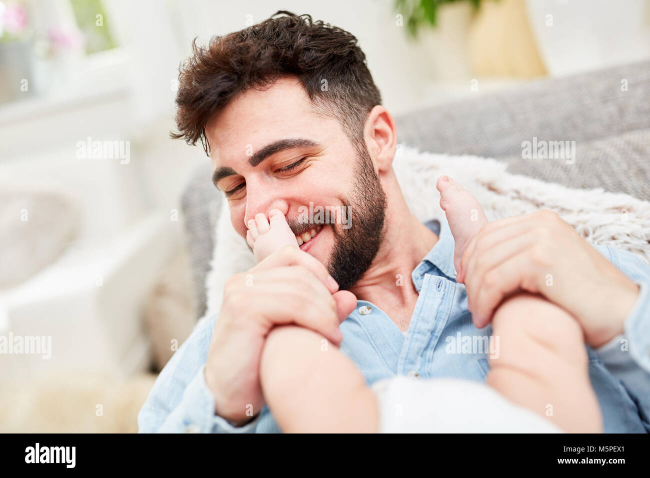 Happy father plays and cuddles with his newborn baby - Stock Image