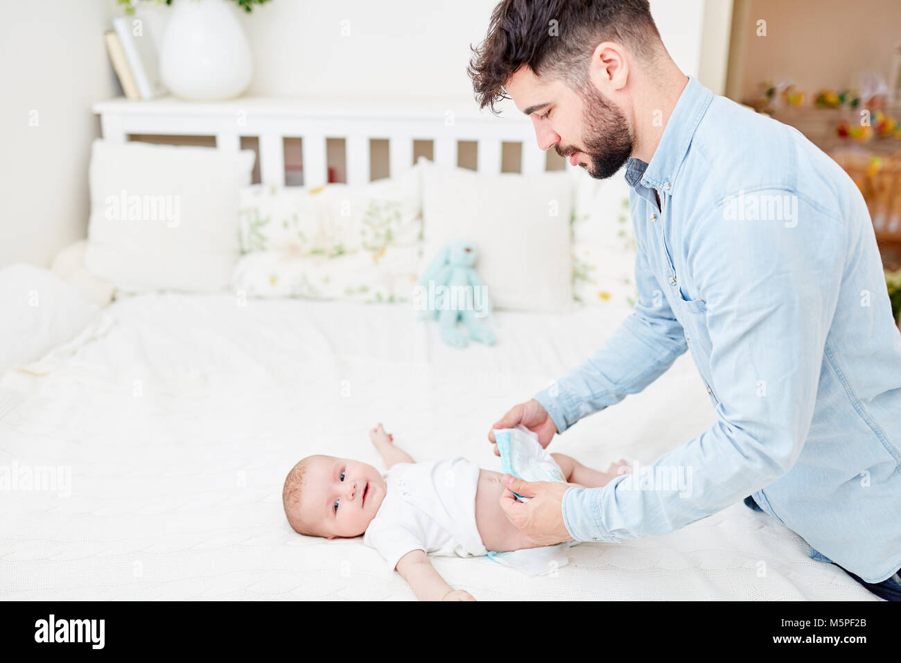 Young man as father in parental leave changes the diapers of his baby - Stock Image