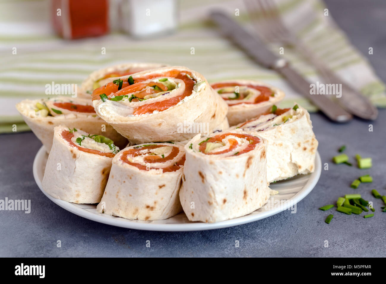Rolls of thin pancakes with smoked salmon, cream cheese, chives and lettuce. - Stock Image