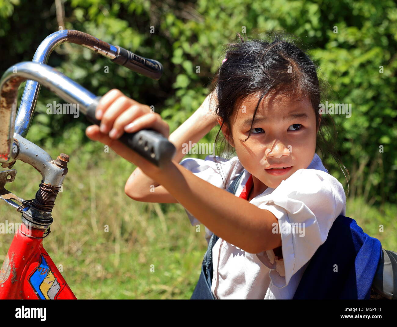 KHON,LAOS-OCTOBER 16, 2015:  Small school conducted by bike along the path to school on October 16, Khon, Laos. - Stock Image