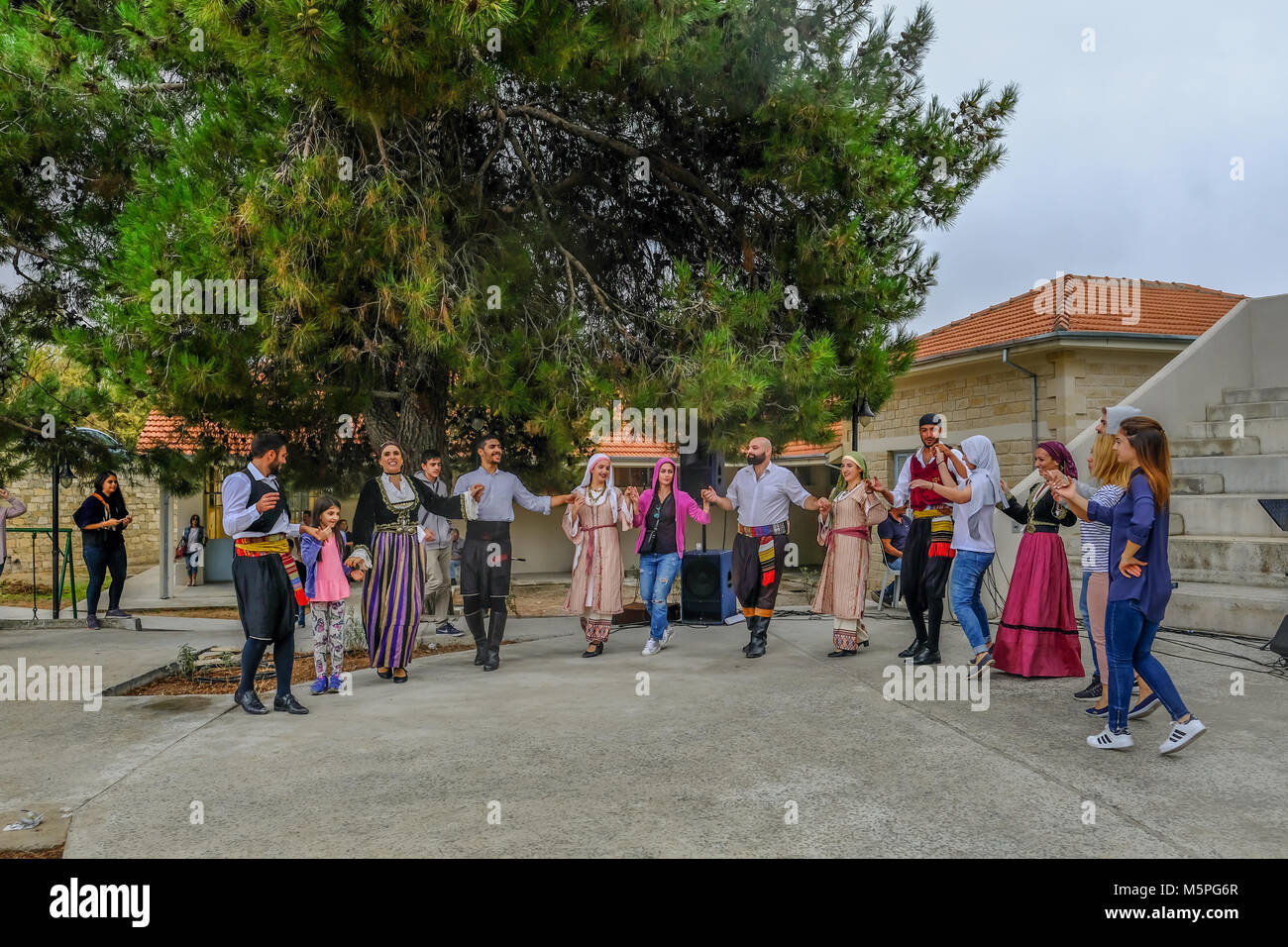 Arsos, Cyprus - October 8, 2017:  Cypriot dancers performing a traditional group dance with audience joining in. - Stock Image