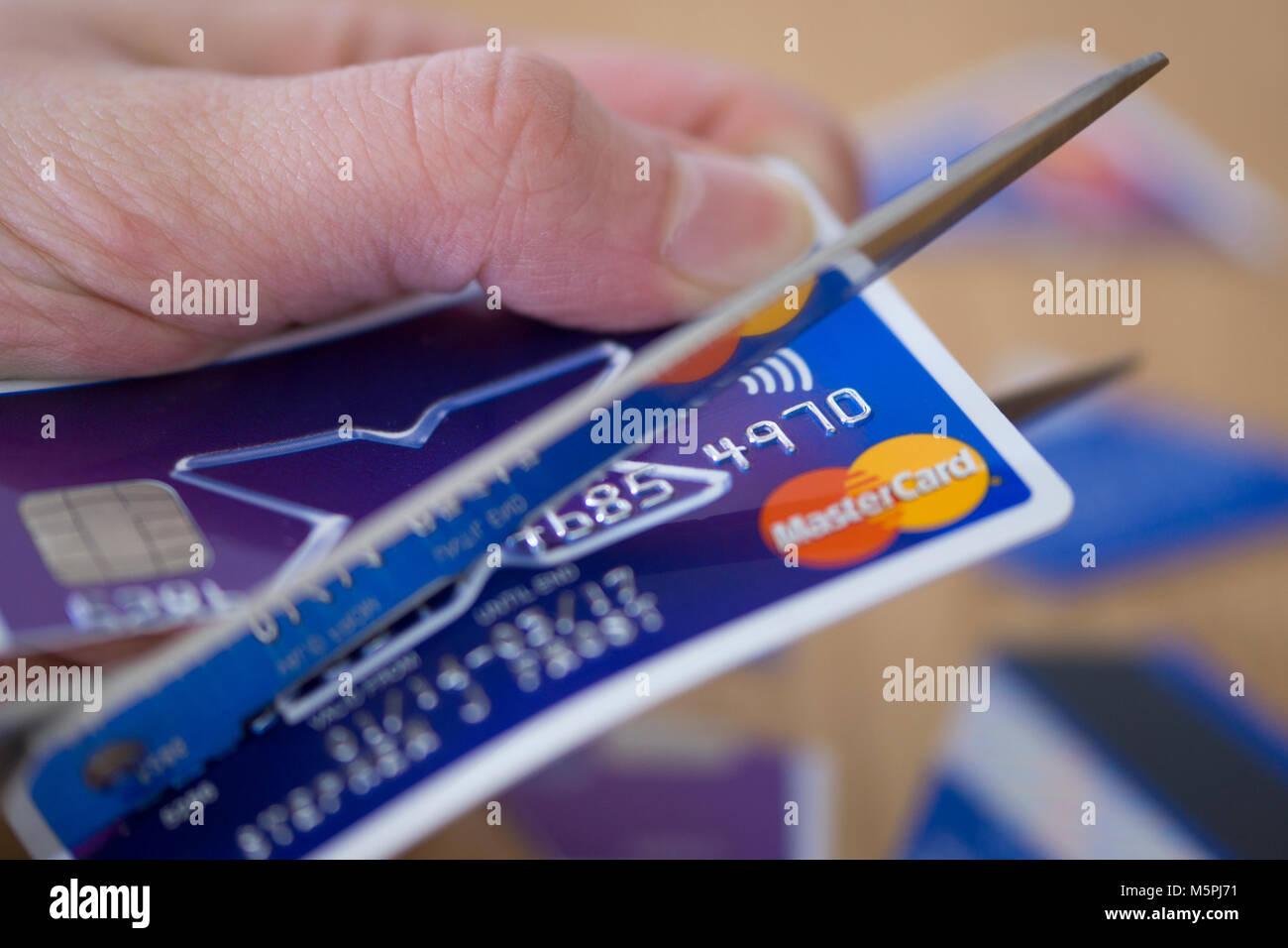 A closeup of a woman cutting up a credit card - credit card debt concept - Stock Image