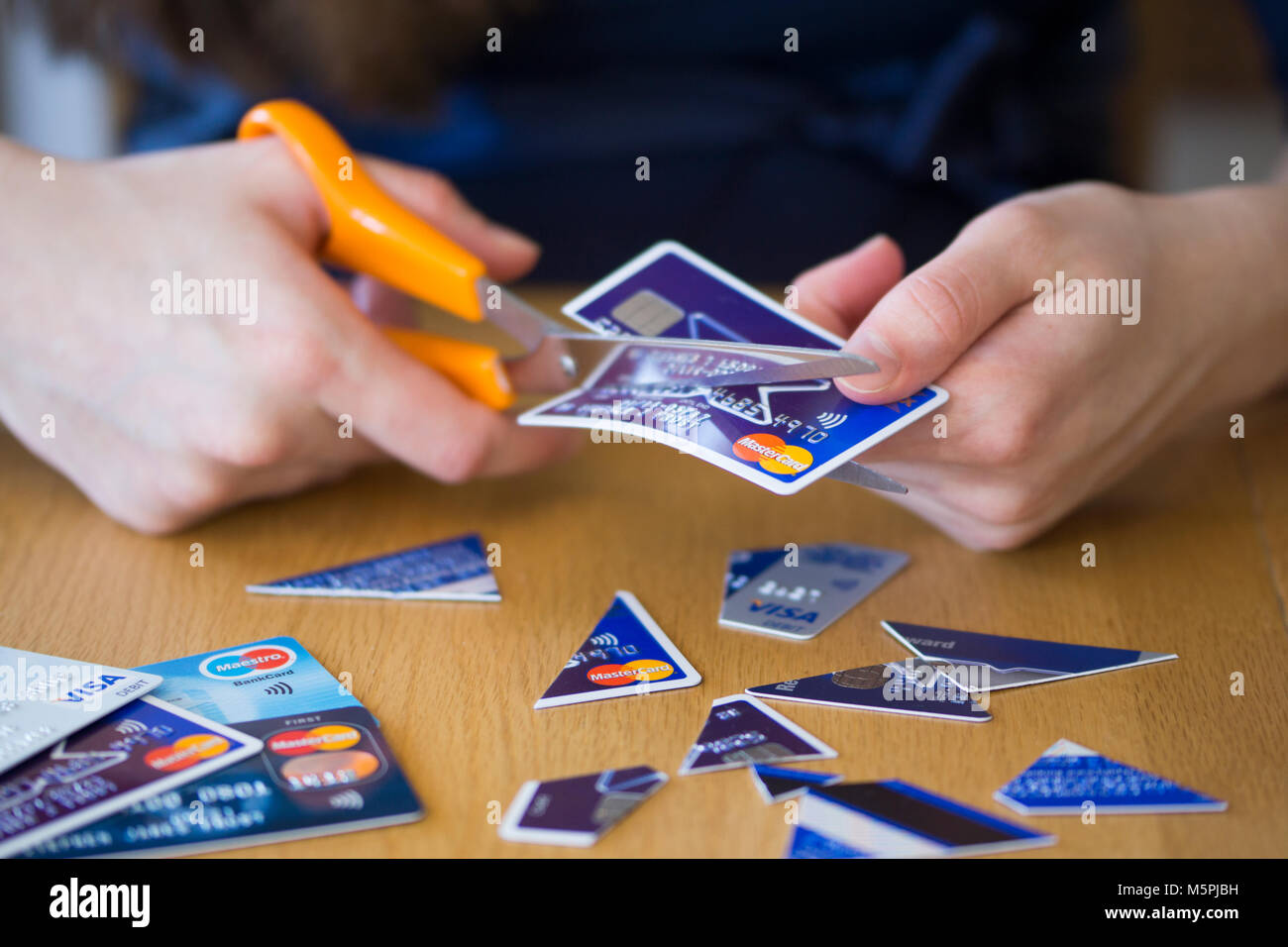 A woman cutting up credit cards - credit card debt concept - Stock Image