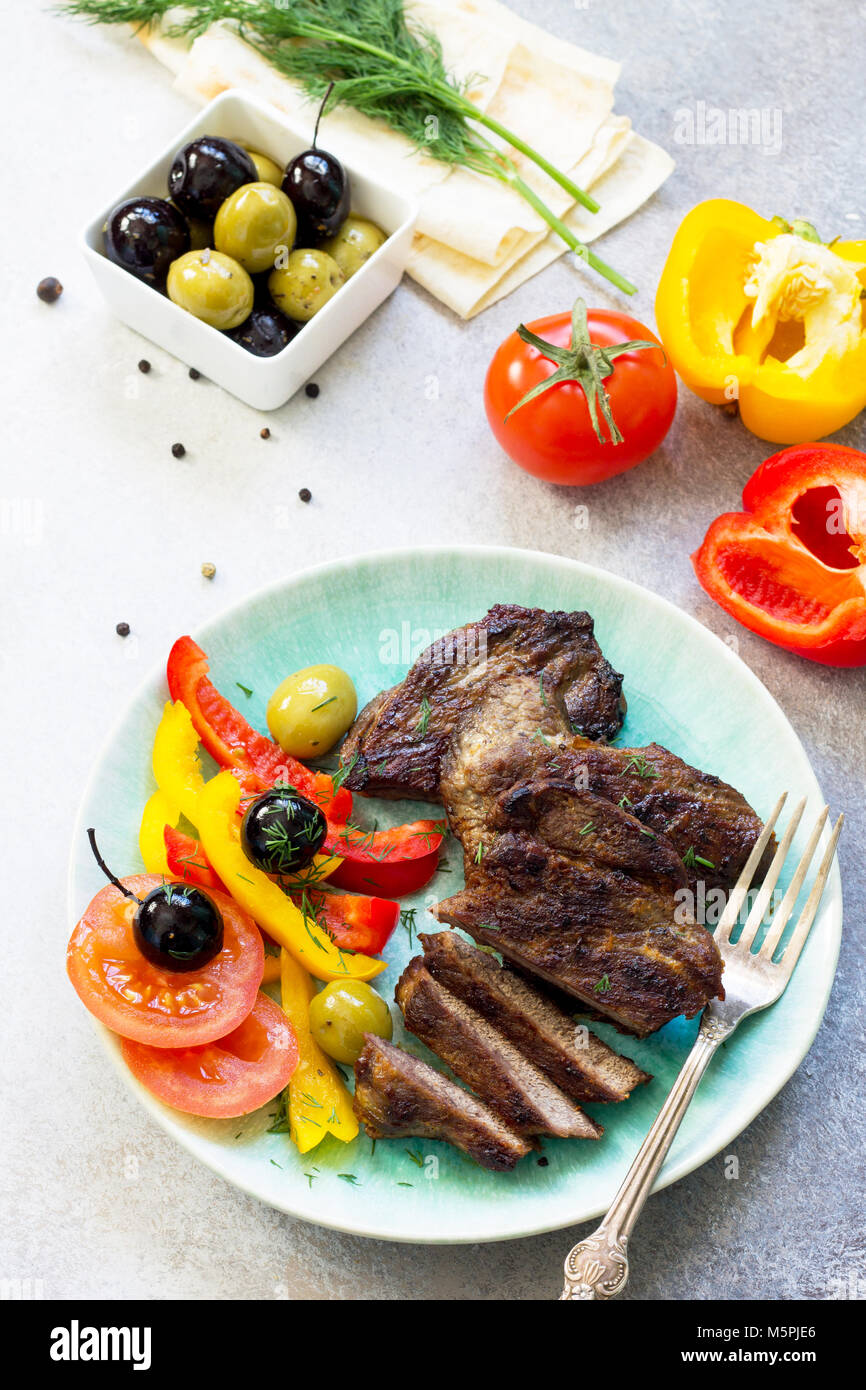 Appetizing barbecue steak from beef sirloin full roast served with fresh vegetable salad. Stock Photo