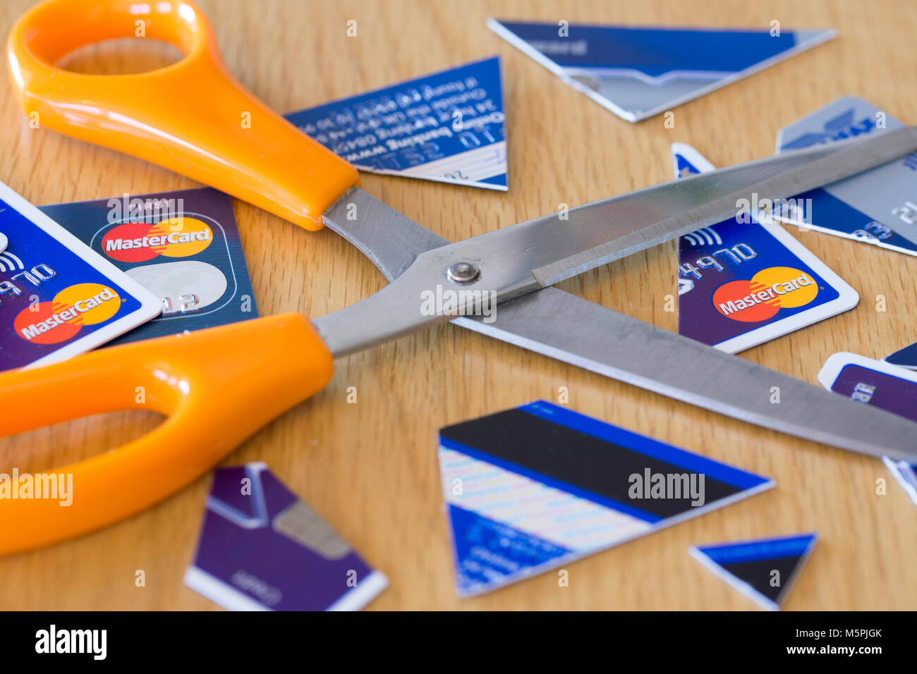 A pair of scissors in the middle of cut up credit cards - credit card debt concept - Stock Image