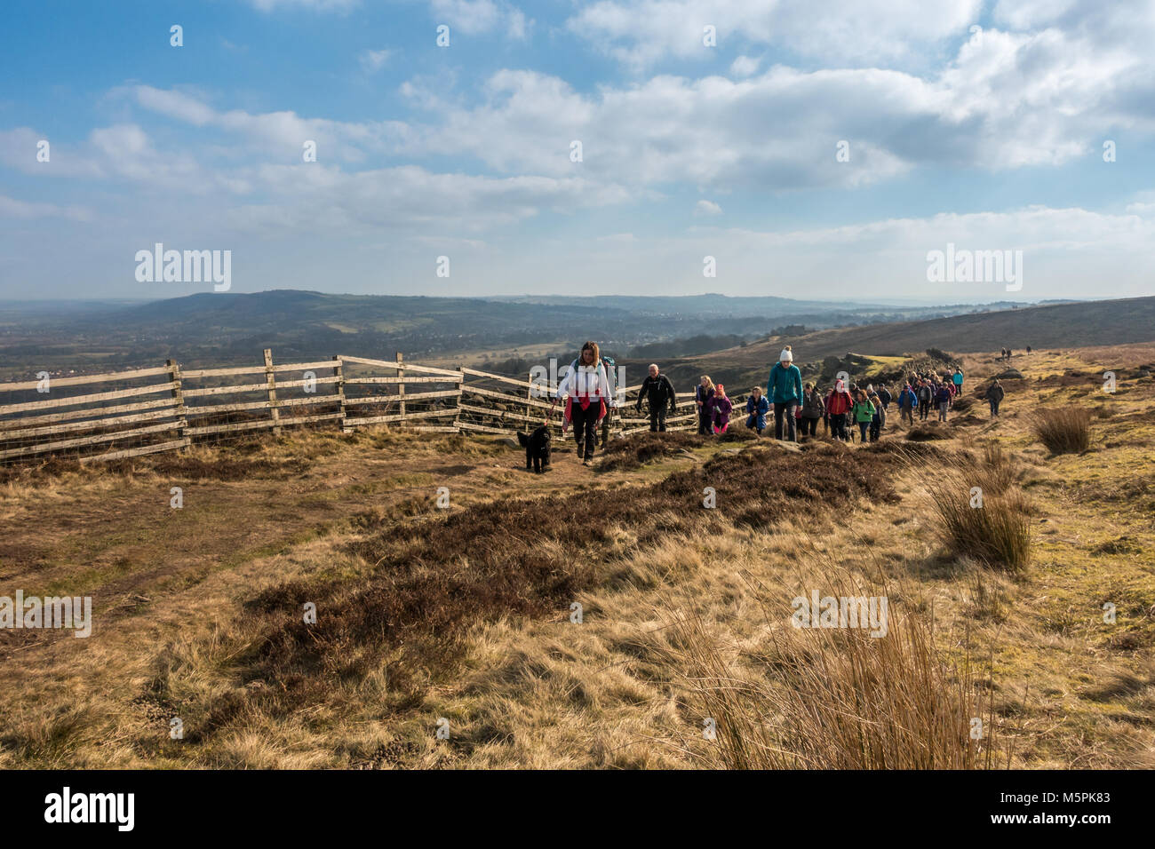 Large group of walkers doing a winter ramble on Ilkley Moor with views of Wharfedale - Stock Image