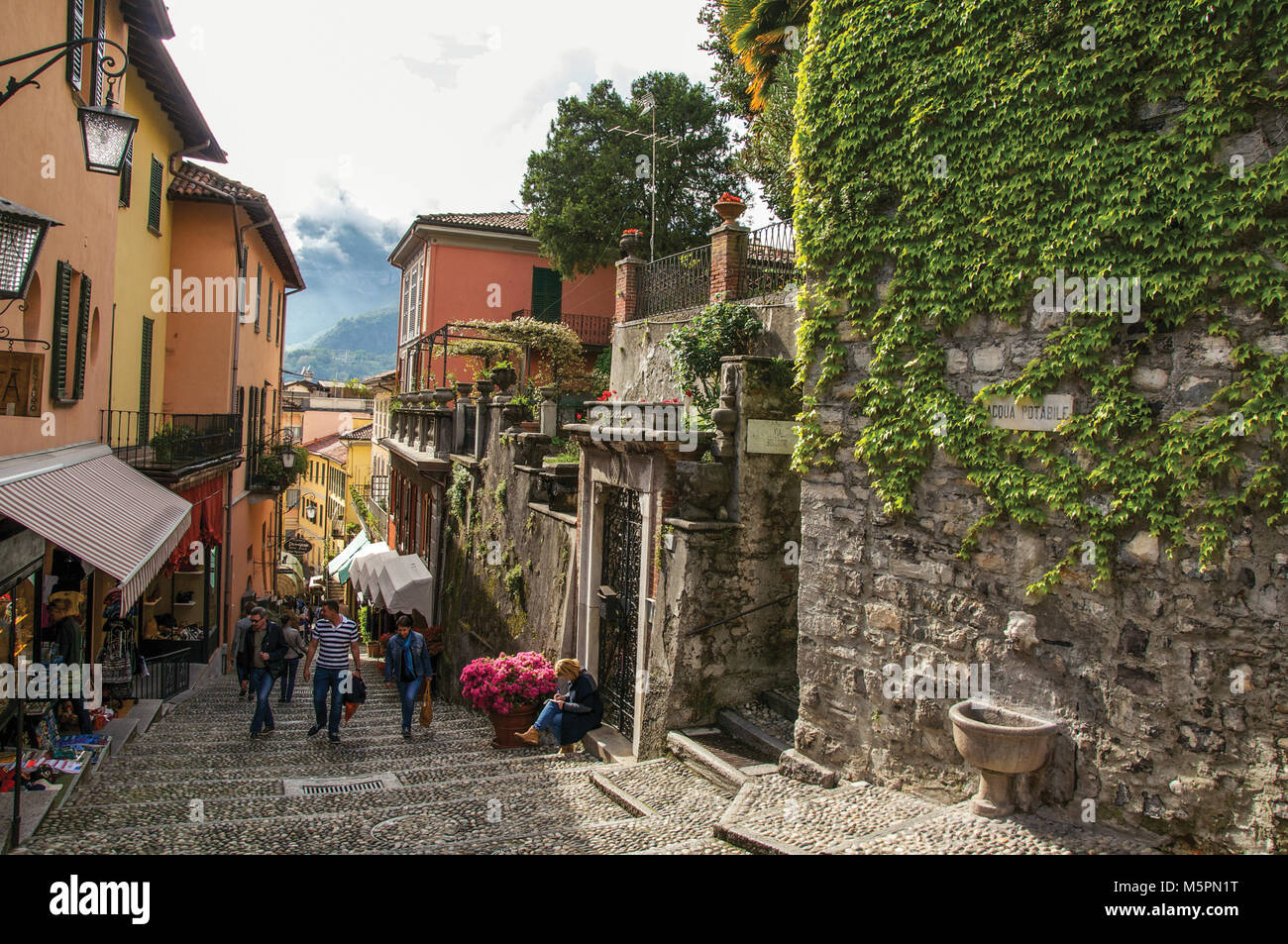Como, Italy. View of alley in hillside, buildings and wall with bindweed in Bellagio, a charming village between - Stock Image
