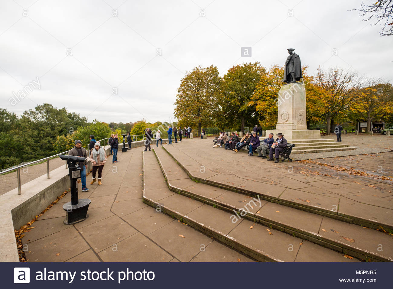 People sitting on benches below General James Wolfe Statue in Greenwich Park, Greenwich, London, England, United - Stock Image